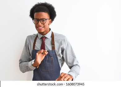 Young african american shopkeeper man wearing apron glasses over isolated white background disgusted expression, displeased and fearful doing disgust face because aversion reaction. With hands raised