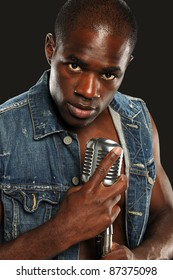 Young African American Singer holding a vintage microphone isolated on a dark background