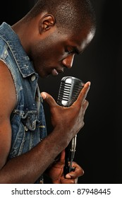 Young African American Singer with vintage microphone isolated on a dark background