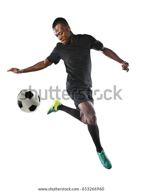 Young African American soccer player kicking ball inside large stadium