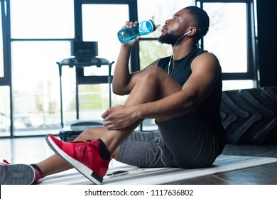 young african american sportsman in earphones sitting on yoga mat and drinking water in gym