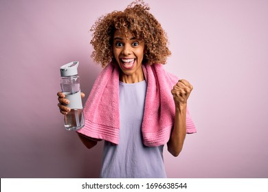 Young african american sportswoman doing sport wearing towel drinking bottle of water screaming proud and celebrating victory and success very excited, cheering emotion