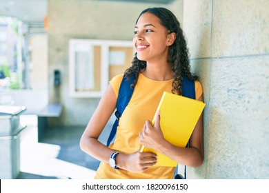Young african american student smiling happy and holding book at university.
