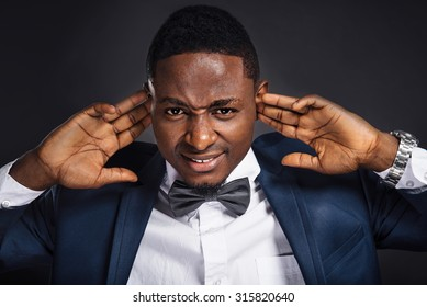 Young african american in suit man close his ears with hands and does not want to hear anything