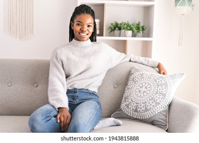 A young African American teen on a sofa in her living room relaxing