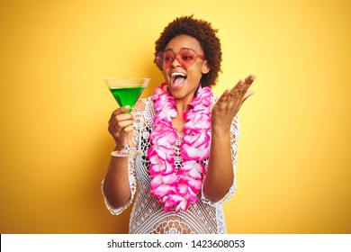 Young african american woman with afro hair wearing flower hawaiian lei and drinking a cocktail very happy and excited, winner expression celebrating victory screaming with big smile and raised hands