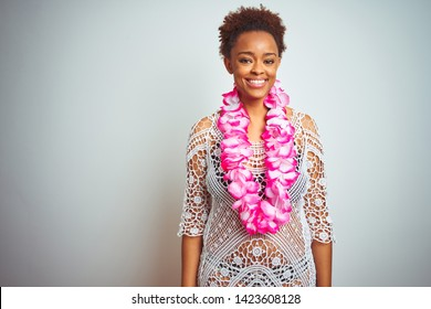 Young african american woman with afro hair wearing flower hawaiian lei over isolated background with a happy and cool smile on face. Lucky person.