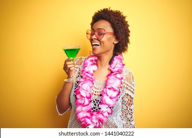Young african american woman with afro hair wearing flower hawaiian lei and drinking a cocktail with a happy face standing and smiling with a confident smile showing teeth