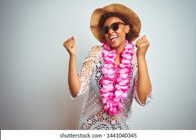 Young african american woman with afro hair wearing flower hawaiian lei over isolated background celebrating surprised and amazed for success with arms raised and open eyes. Winner concept.