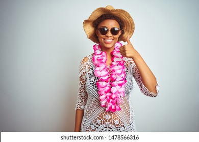Young african american woman with afro hair wearing flower hawaiian lei over isolated background doing happy thumbs up gesture with hand. Approving expression looking at the camera