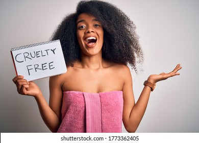 Young african american woman with afro hair wearing a towel asking for cruelty free beauty very happy and excited, winner expression celebrating victory screaming with big smile and raised hands