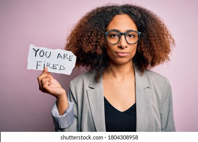 Young african american woman with afro hair holding paper with you are fired message with a confident expression on smart face thinking serious