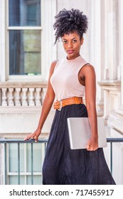 Young African American woman with afro hairstyle wearing sleeveless light color top, belt, black skirt, holding laptop computer, standing in vintage office building in New York, looking at you.