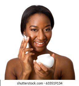 young african american woman applying cream to her face