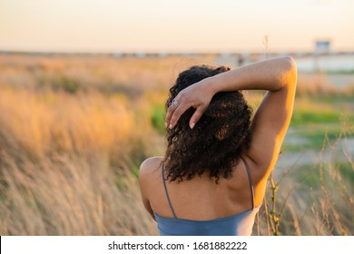 young african american woman from back touching her hair
