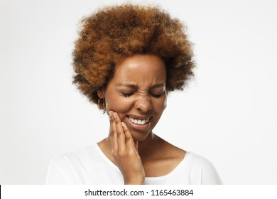 Young african american woman in blank white t shirt, isolated on gray background, touching her face with expression of horrible suffer from health problem and aching tooth