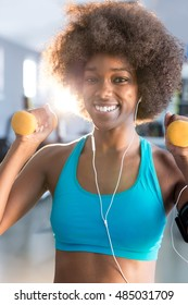 young african american woman in blue sportswear doing weight lifting in fitness club
