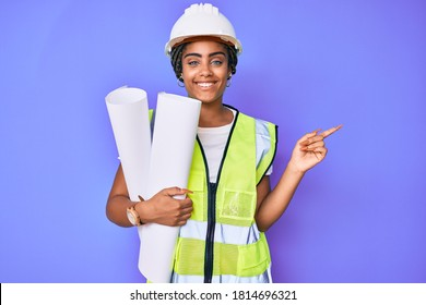 Young african american woman with braids wearing safety helmet holding blueprints smiling happy pointing with hand and finger to the side