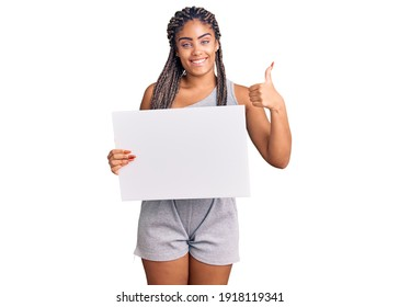 Young african american woman with braids holding blank empty banner smiling happy and positive, thumb up doing excellent and approval sign