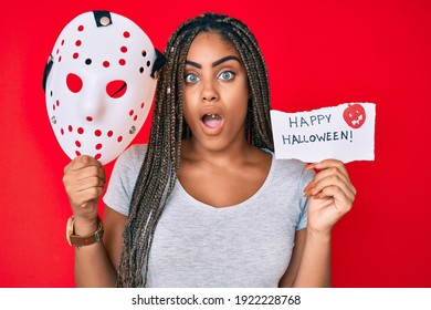 Young african american woman with braids holding halloween banner and scary mask afraid and shocked with surprise and amazed expression, fear and excited face.