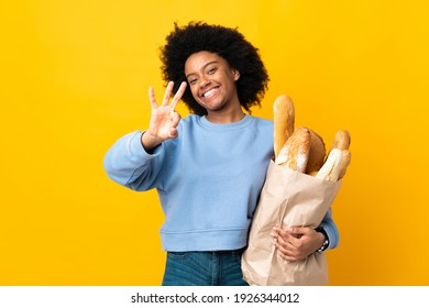 Young African American woman buying something bread isolated on yellow background happy and counting three with fingers