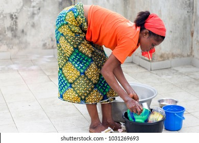 young african american woman doing the dishes in the yard of the house