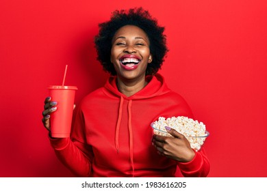 Young african american woman eating popcorn and drinking soda smiling and laughing hard out loud because funny crazy joke.