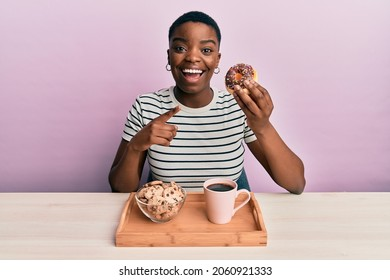 Young african american woman eating breakfast holding chocolate donut smiling happy pointing with hand and finger