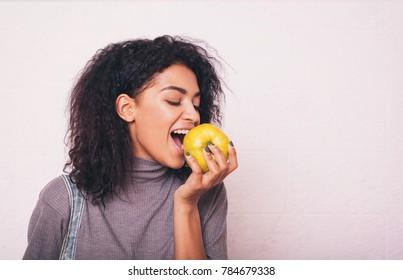 Junge afrikanische Amerikanerin isst Apfel