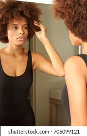 Young African American woman getting ready for work in mirror