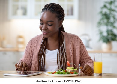 Young African American Woman Having Breakfast In Kicthen And Using Digital Tablet, Smiling Black Lady Browsing New Application Or Shopping Online In Internet While Eating Tasty Food, Free Space