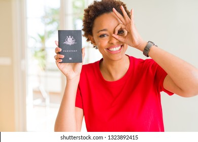 Young african american woman holding Australian passport with happy face smiling doing ok sign with hand on eye looking through fingers