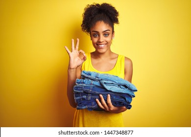 Young african american woman holding stack of jeans over isolated yellow background doing ok sign with fingers, excellent symbol