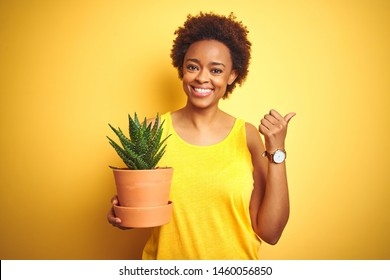 Young african american woman holding cactus pot over isolated yellow background pointing and showing with thumb up to the side with happy face smiling
