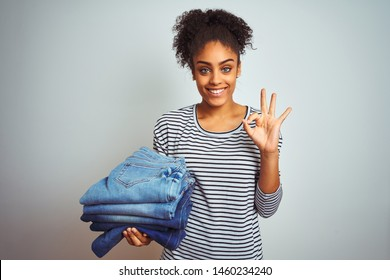 Young african american woman holding stack of jeans over isolated white background doing ok sign with fingers, excellent symbol
