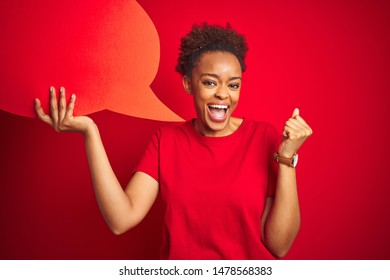 Young african american woman holding speech bubble over red isolated background screaming proud and celebrating victory and success very excited, cheering emotion