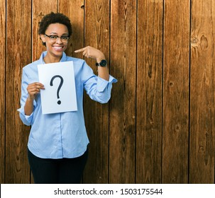 Young african american woman holding paper with question mark over isolated background with surprise face pointing finger to himself