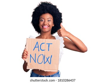 Young african american woman holding act now banner smiling happy and positive, thumb up doing excellent and approval sign