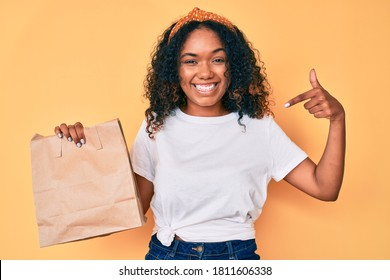 Young african american woman holding take away paper bag pointing finger to one self smiling happy and proud