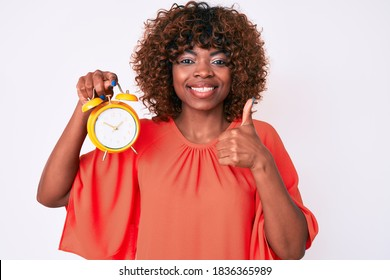 Young african american woman holding alarm clock smiling happy and positive, thumb up doing excellent and approval sign