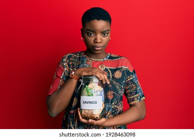 Young african american woman holding savings jar with south african rands money skeptic and nervous, frowning upset because of problem. negative person.