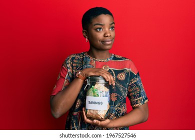 Young african american woman holding savings jar with south african rands money smiling looking to the side and staring away thinking.