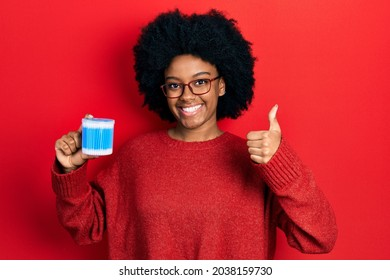 Young african american woman holding earwax cotton remover smiling happy and positive, thumb up doing excellent and approval sign