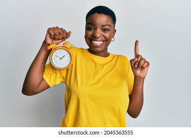 Young african american woman holding alarm clock smiling with an idea or question pointing finger with happy face, number one