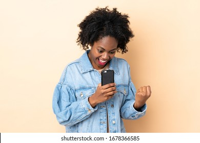Young African American woman isolated on beige background surprised and sending a message