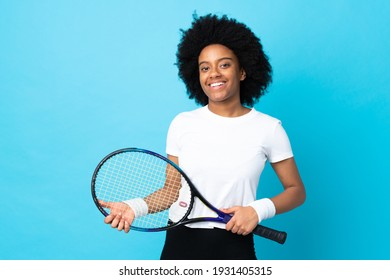 Young African American woman isolated on blue background playing tennis