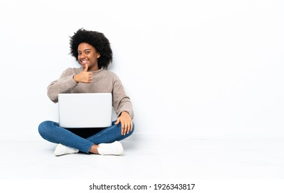 Young African American woman with a laptop sitting on the floor giving a thumbs up gesture