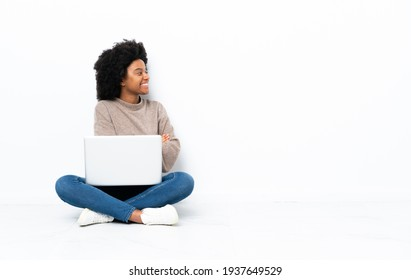 Young African American woman with a laptop sitting on the floor in lateral position