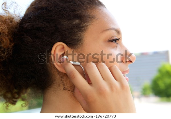 Young african american woman listening to music with earphones in ears