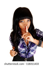 A young African American woman with long curly black hair in closeup gesturing be quiet, for white background with one finger on her mouth.